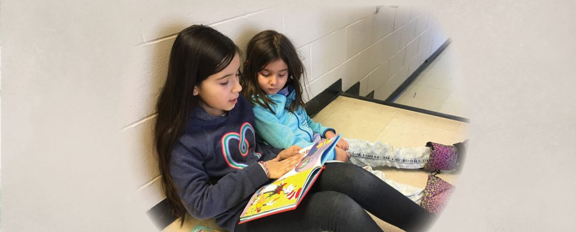 two girls reading a book in the hallway